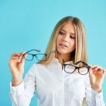 Pensive businesswoman with glasses standing before blue background