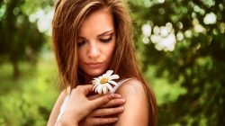 young beautiful woman outdoor in a birchwood with daisy flowers