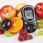 Glucose meter with result of measurement sugar level and fresh fruits, diabetes and healthy nutrition